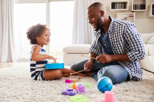 Young black father playing with daughter in the sitting room